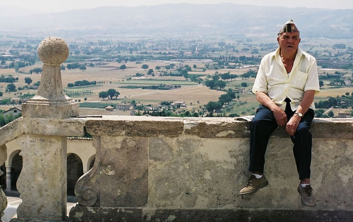 An old-timer rests on a ledge in Assisi